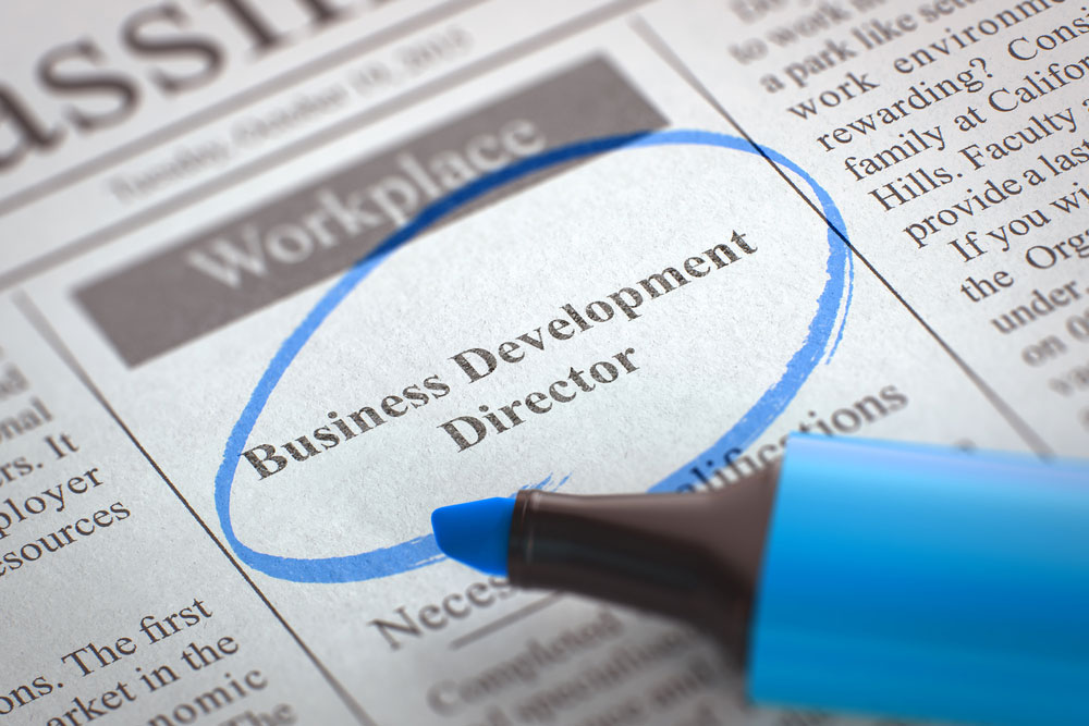 A newspaper ad for business development director circled with a blue marker