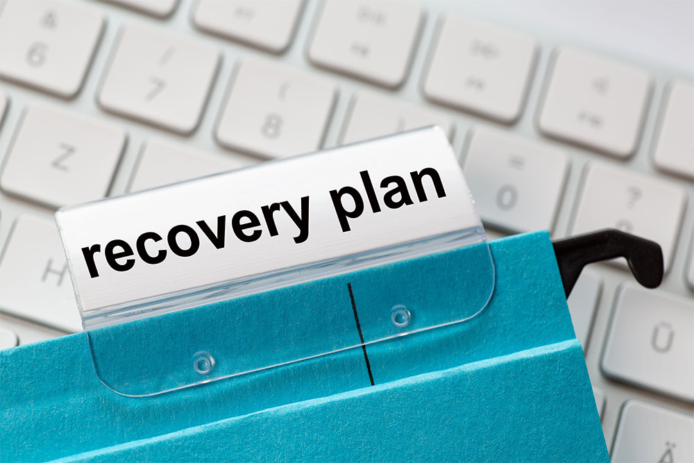 Recovery plan on a label of a blue hanging file for business turnaround strategies.
