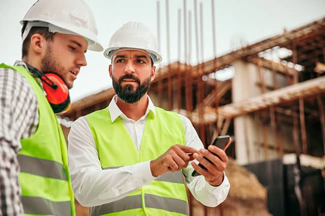 Two construction workers use a digital app on a construction site